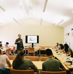 Professor Dan Edelstein delivers a lecture to a room of participants.