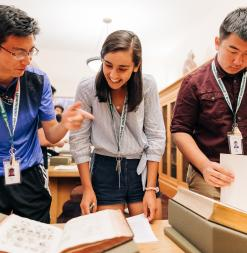 Three students examine rare print materials in Stanford Special Collections.