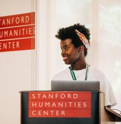 A student reads at a podium at the Stanford Humanities Center.